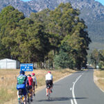 Four cyclists riding on the left side of a long road with no cars, with granite mountains in the distance