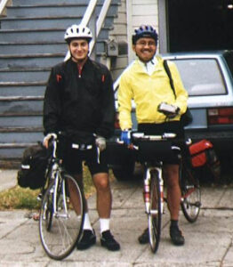 Two cyclists holding their with panniers, one dressed in black, one in yellow.