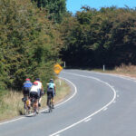 Four cyclists riding on the left side of a curving road with no traffic